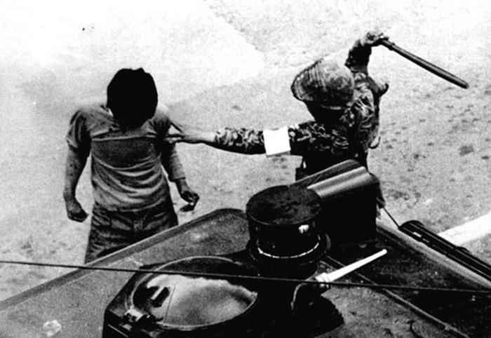 사진: 5.18 민주화 운동 당시 계엄군이 몽둥이로 시민을 폭행하고 있는 사진. [안병하 경찰국장과 5.18 광주 민주화 운동]