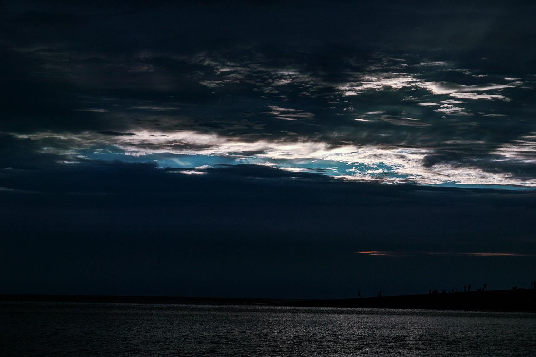 을왕리해수욕장-먹구름이 하늘을 덮어 온통 어둡고 아직 덮히지 않은 일부 하늘만 해가 보이는 사진